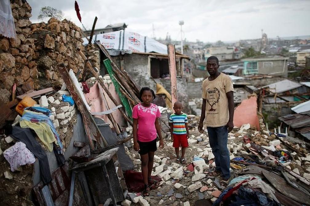 Família em meio a destroços após passagem do furacão Matthew no Haiti. (Foto: REUTERS/Carlos Garcia Rawlins/Files)