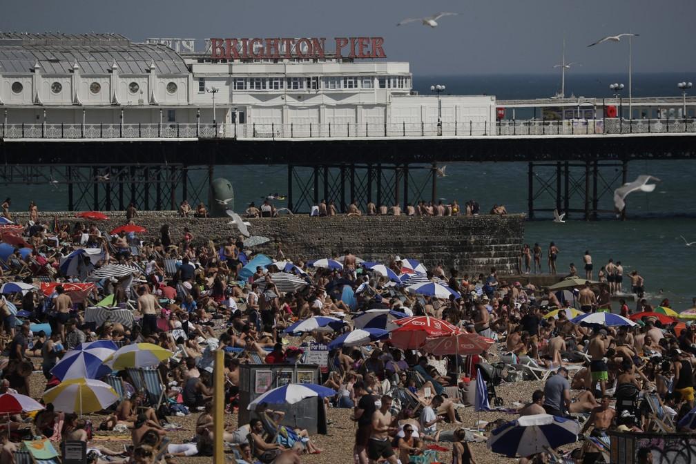 Centenas de pessoas lotam praia em Brighton, no sul da Inglaterra, nesta quarta-feira (24) — Foto: Matt Dunham/AP Photo