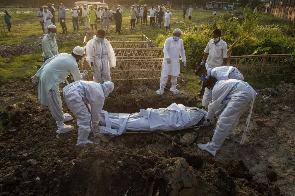 Funcionários municipais se preparam para enterrar o corpo de vítima da Covid-19 em Gauhati, na Índia, em 25 de abril de 2021 — Foto: Anupam Nath/AP