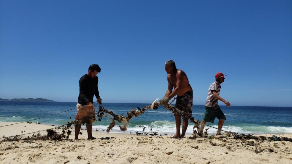 Alexandre Pereira, pescador (ao centro da foto) de Maricá, diz que a ganância faz com que pescadores avancem com as embarcações a motor para perto da praia — Foto: Anna Beatriz Lourenço/G1