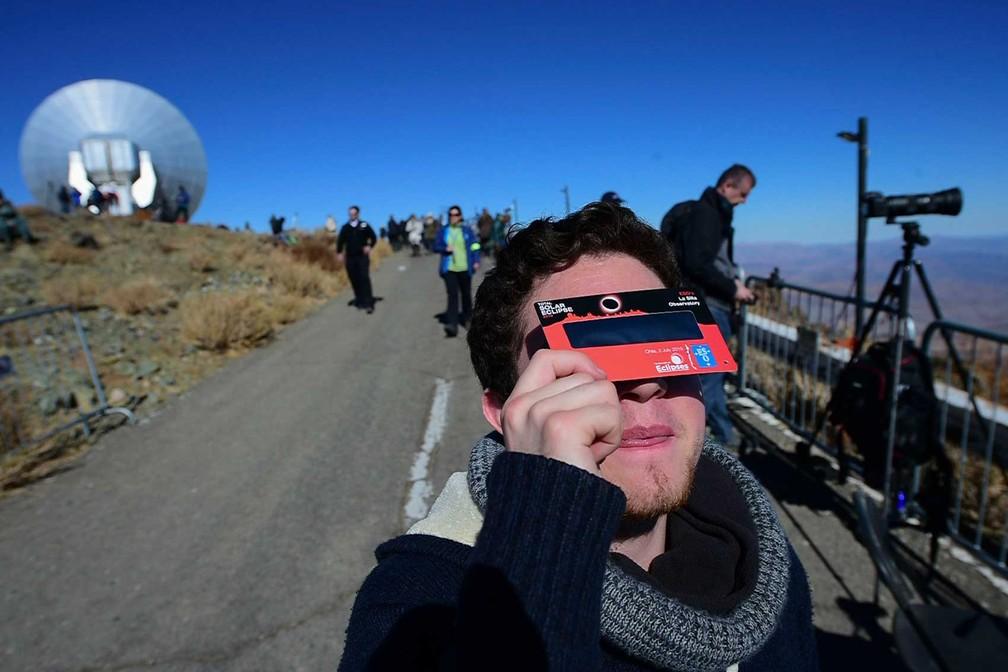 Eclipse 2019 - turista em observatório no Chile protege os olhos com óculos especial. Fenômeno não deve ser observado diretamente. — Foto: Martin Bernetti/AFP
