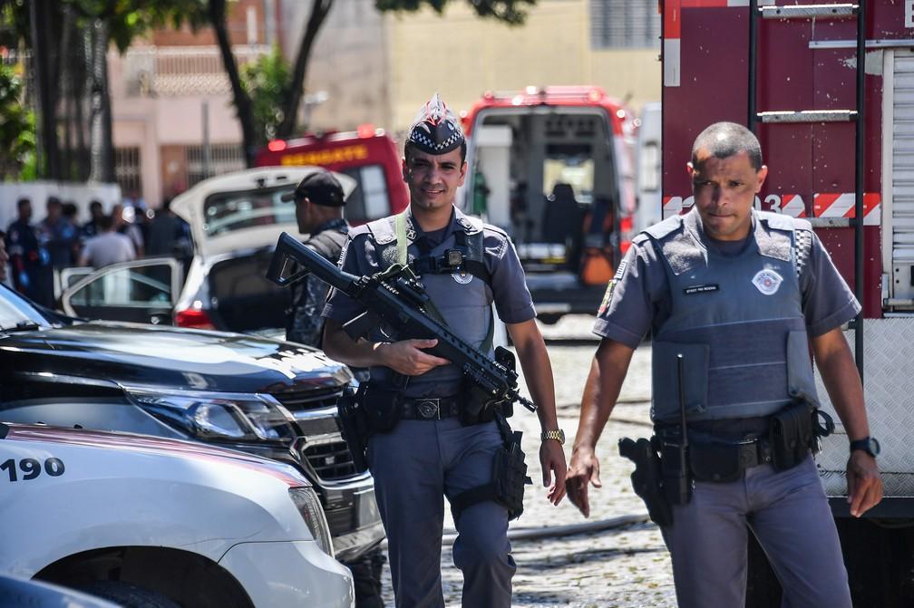 Policiais trabalham nos arredores da Escola Estadual Raul Brasil em Suzano, na Grande São Paulo. Dois criminosos encapuzados mataram oito pessoas no local e cometeram suicídio em seguida — Foto: Nelson Almeida/AFP