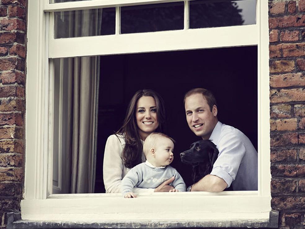 Em foto de 29 de março de 2014, o príncipe William, a princesa Kate, o filho George e o cachorro Lupo posam na janela do Palácio de Kensington, no Reino Unido (Foto: Jason Bell/Camera Press/Kensington Palace/AFP)