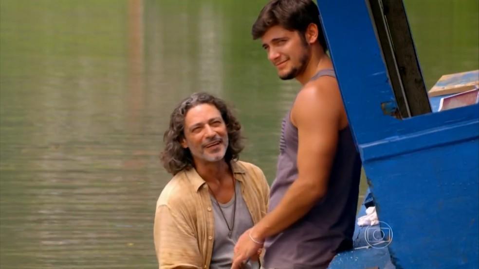 Juliano (Bruno Gissoni) mostra a Donato (Luiz Carlos Vasconcelos) que está interessado em Natália (Daniela Escobar) - 'Flor do Caribe' — Foto: Globo