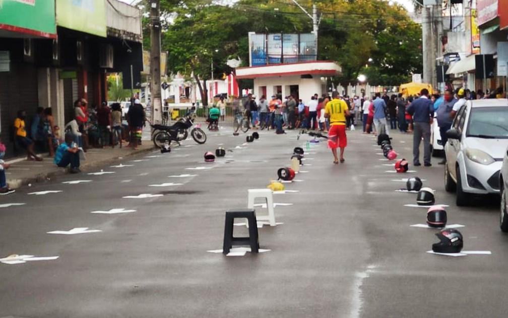Moradores de Ipiaú, na Bahia, usam capacetes e bancos plásticos para marcar lugar em fila de agência  — Foto: Site Giro Ipiaú