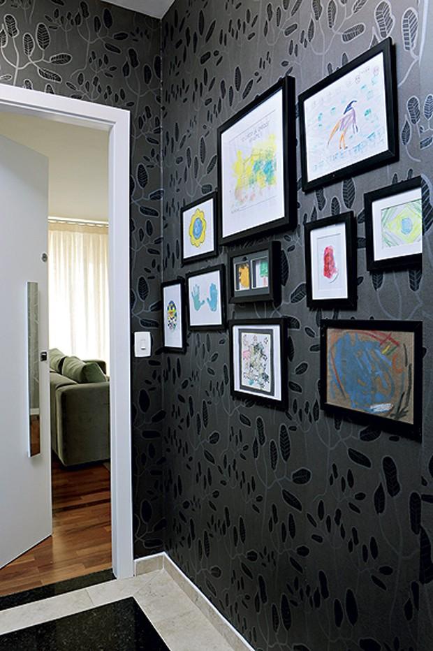 Para expor os desenhos do filho da moradora no hall de entrada, o designer de interiores Gabriel Valdivieso usou molduras pretas de diferentes tamanhos e os colocou de forma assimétrica na parede, toda revestida com papel de parede preto (Foto: Arquivo Casa e Jardim)