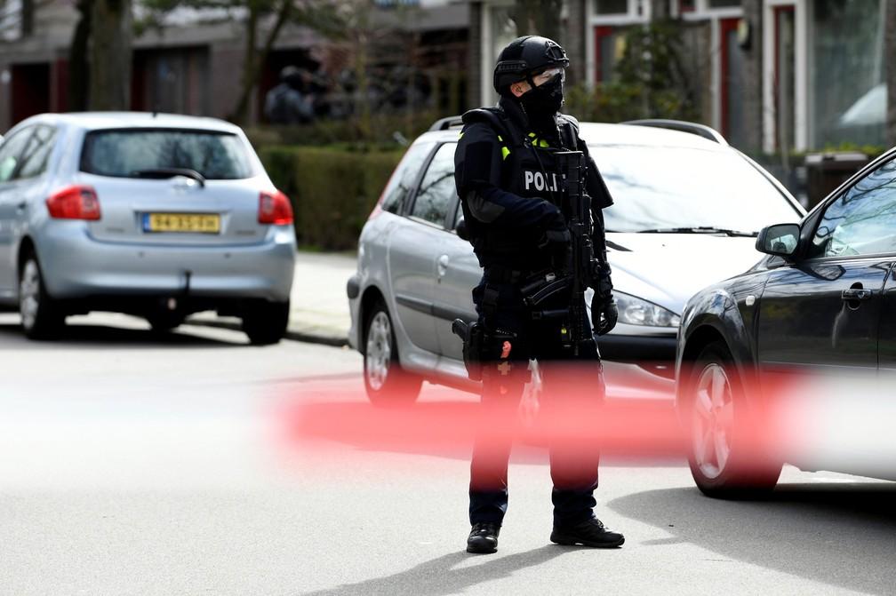 Policial observa carros após tiros no centro de Utrecht, na Holanda — Foto: Piroschka van de Wouw/Reuters