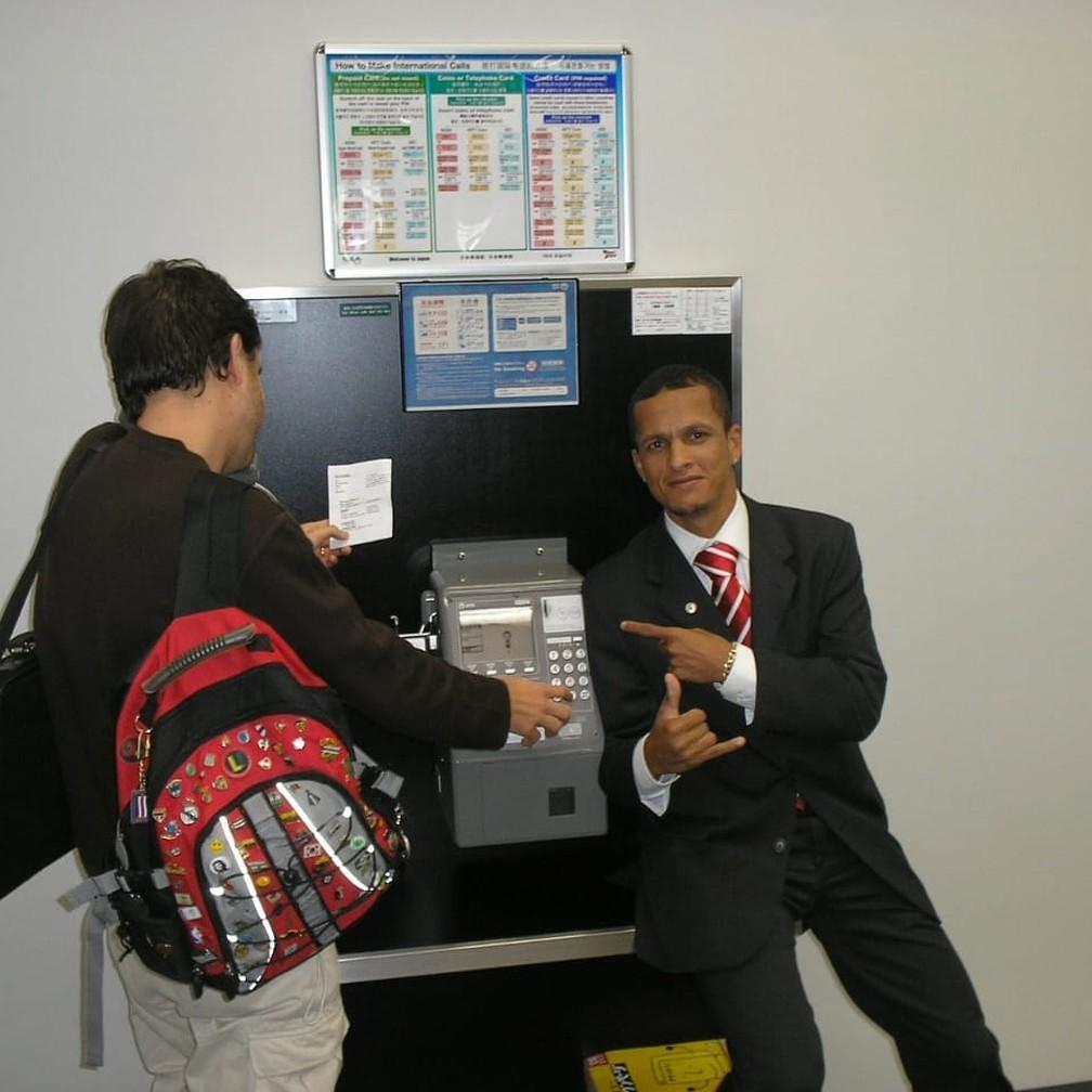 Souza posa ao lado de telefone público no Japão — Foto: Arquivo Pessoal Souza