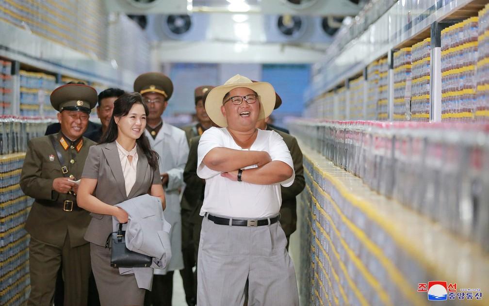 O líder norte-coreano Kim Jong-Un visita uma fábrica, acompanhado por militares e por sua mulher, Ri Sol-ju, em foto não datada divulgada pela agência estatal KCNA (Foto: KCNA via Reuters)