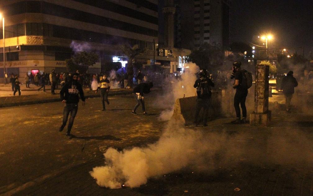 Manifestantes são vistos em meio a fumaça de bombas de gás durante protesto contra lockdown em Tripoli, no Líbano, na noite de quarta-feira (27) — Foto: Reuters/Omar Ibrahim