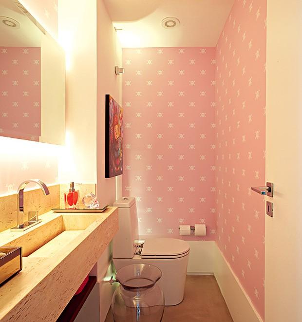 Em um apartamento de cores intensas, a arquiteta Carol Lovisaro, da Lovisaro Arquitetura e Design, criou um lavabo todo em cor-de-rosa com um papel de parede. A iluminação de xenon, embutida atrás do espelho, tem uma luz mais suave e evita que a cor se torne cansativa (Foto: Edu Castello e Lufe Gomes)