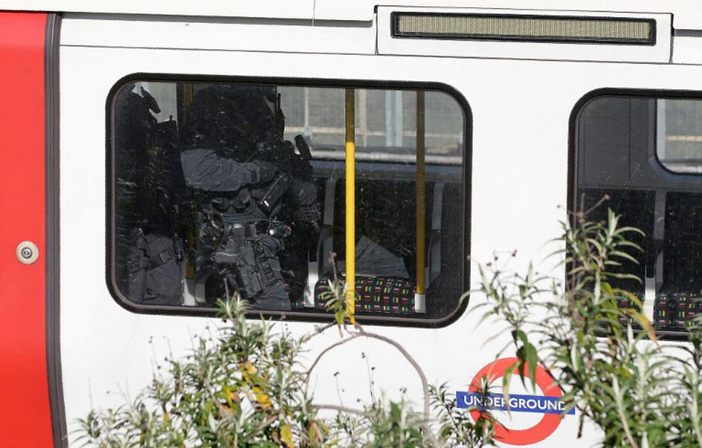 Polícia britânica entram em vagão de trem após explosão em trem na estação Parsons Green, em Londres, nesta sexta-feira (15)  (Foto: Daniel Leal-Olivas / AFP)