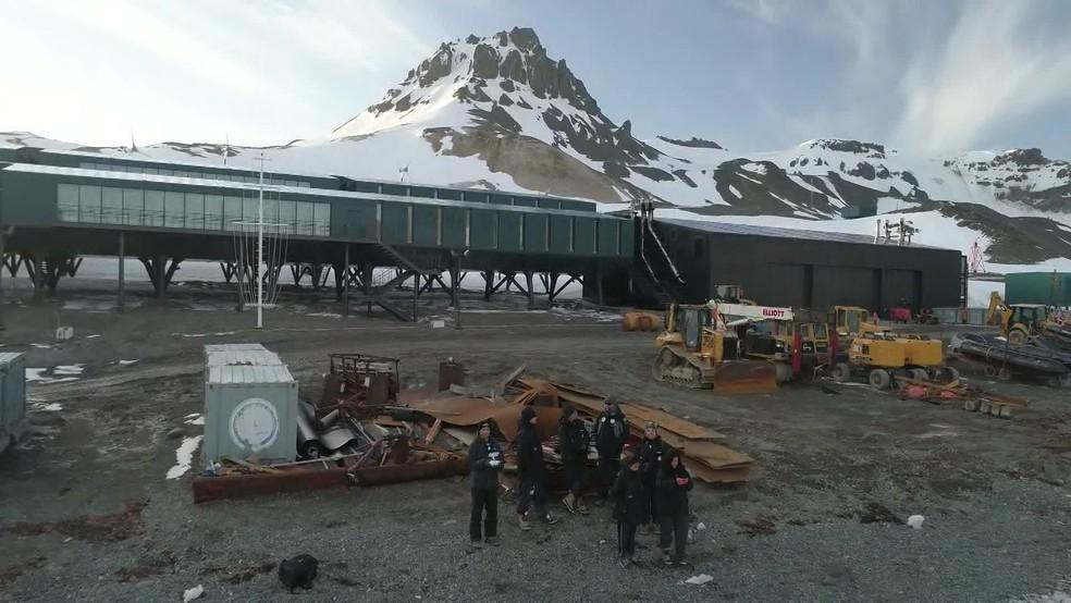 Equipe de pesquisadores posa em frente a Estação Antártica Comandante Ferraz, que é inaugurada nesta terça (14) — Foto: Reprodução/TV Globo