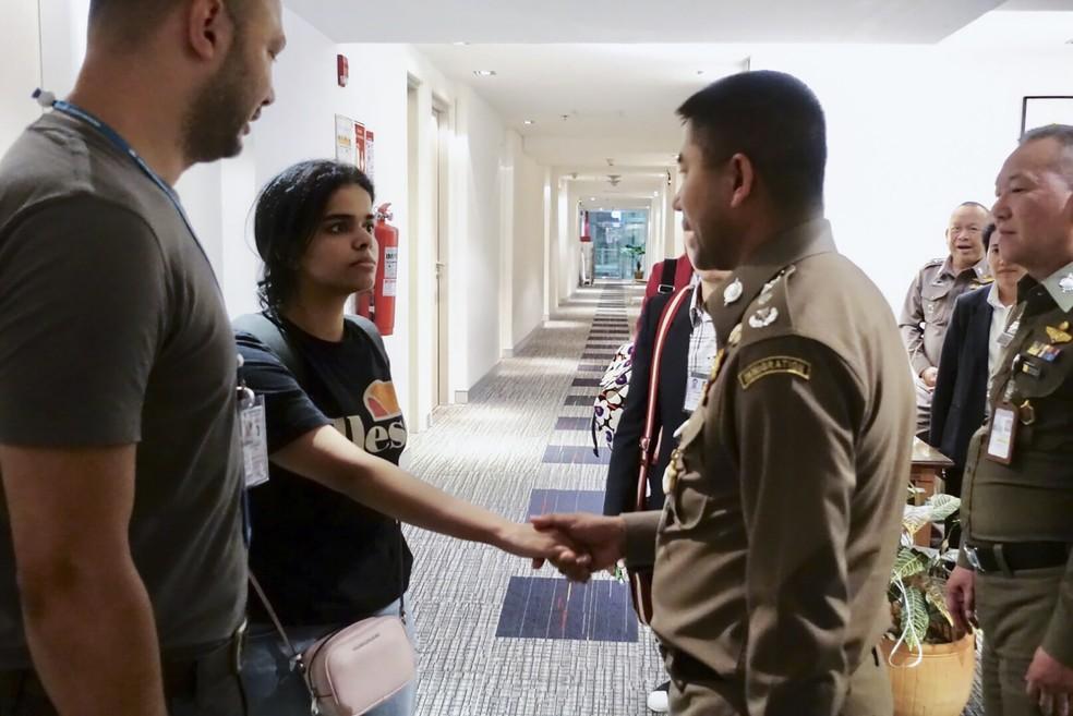 Jovem saudita de 18 anos se encontra com oficiais que a escoltaram para fora do aeroporto de Bangkok, na Tailândia — Foto: Thai Immigration Bureau / AFP