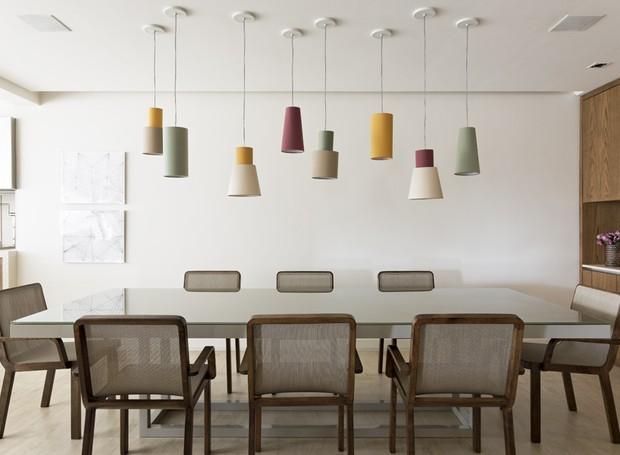 Os pontos de cor aparecem discretamente espalhados pelo apartamento, mas a paleta rica é capaz de aquecer os olhares. Aqui, o mix de cor enfeita as luminárias sobre a mesa de jantar (Foto: Alain Brugier)