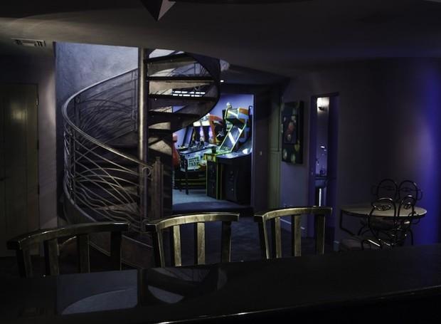 Uma sala de jogos possui um ar macabro com móveis escuros e paredes roxas (Foto: DeCaro Auctions International/ Reprodução)