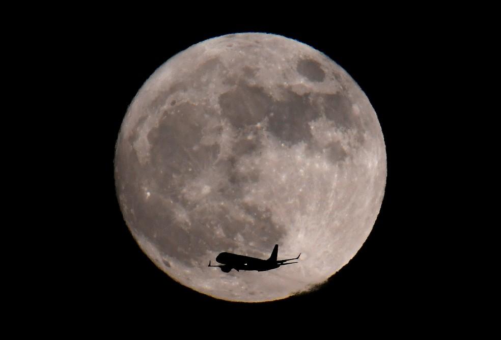 Avião passa pela Superlua próximo a aeroporto em Londres na noite de segunda-feira (1) (Foto: Toby Melville/Reuters)
