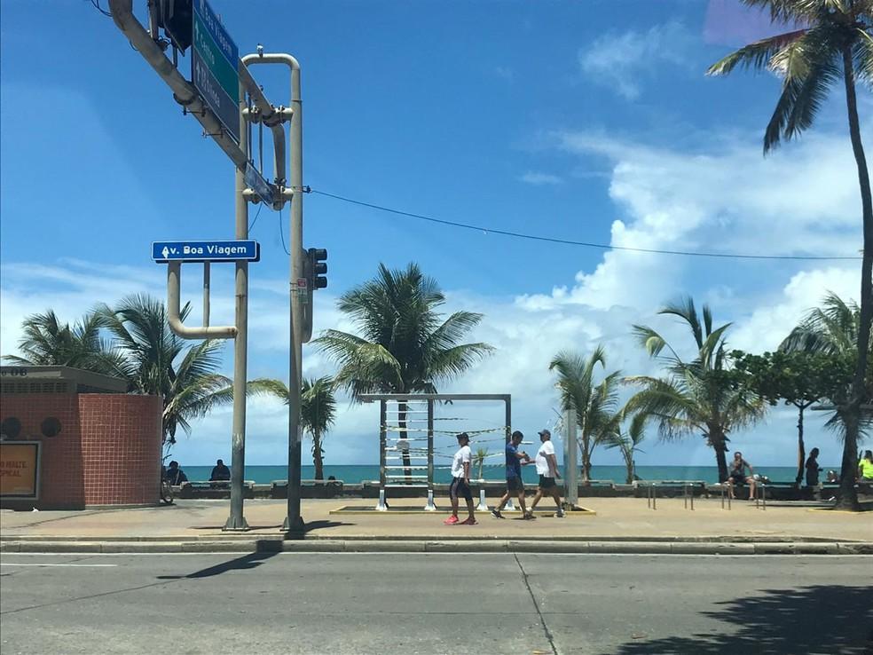 Pedestres caminham na orla de Boa Viagem, na Zona Sul do Recife, e passam por equipamento de ginástica interditado pela prefeitura — Foto: Isabela Veríssimo/G1