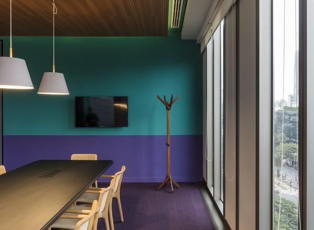 A azul e roxo estampam a parede de uma sala de reuniões. Apesar de serem ambas vibrantes as cores não brigam entre si, por estarem em uma paleta similar. Enquanto isso, as cadeiras de palhinha trazem sofisticação para o ambiente jovial (Foto: estudio guto requena | 2018)