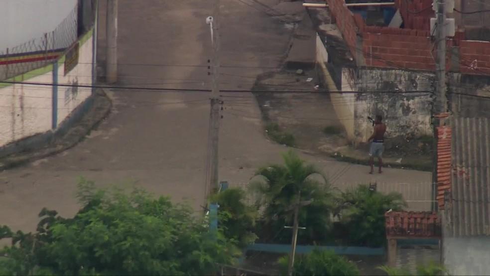 Homem é flagrado pelo Globocop com fuzil atrás de muro na Cidade de Deus, na Zona Oeste do Rio — Foto: Reprodução/ TV Globo