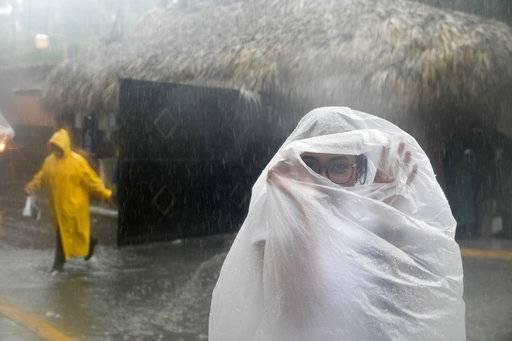 Mulher se protege da chuva em Bávaro, em Punta Cana, na República Dominicana, por onde passa neste momento o furacão Maria