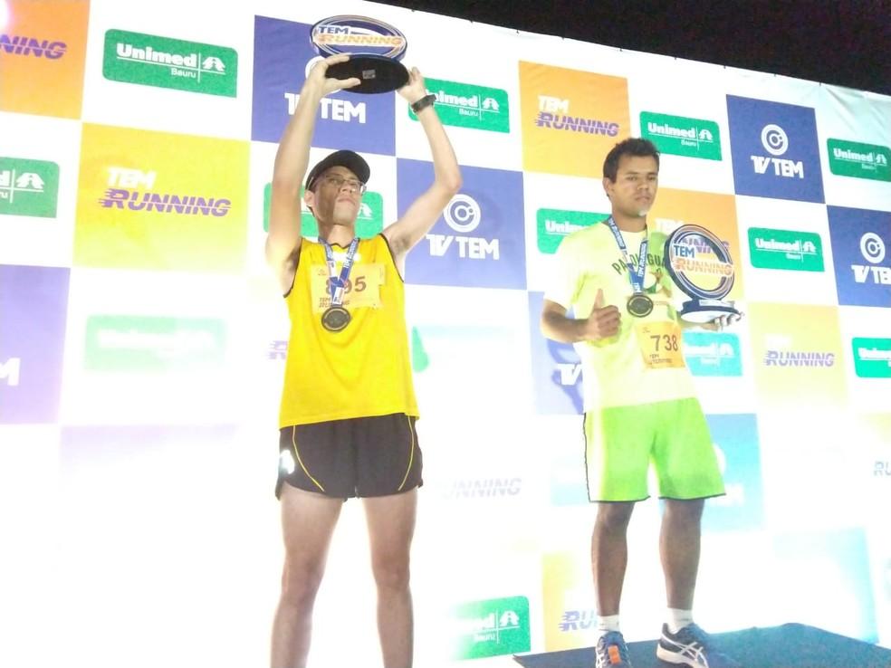 Campeão (à dir.) e vice dos 10 km para PNE (Portadores de Necessidades Especiais) exibem seus troféus: superação (Foto: Sérgio Pais)