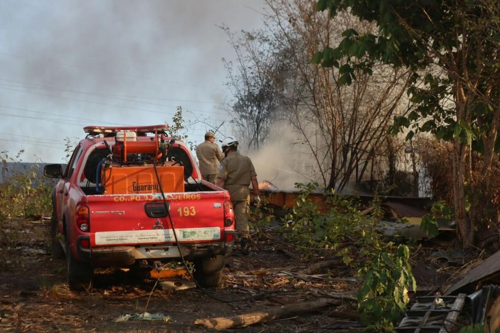 Bombeiros tentam controlar as chamas em sucata — Foto: Stephanie Pacheco