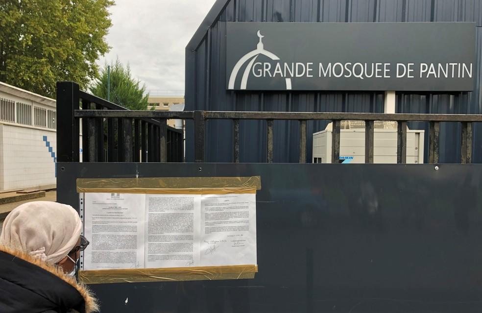 Uma mulher lê um decreto municipal instalado nos portões de entrada da Grande Mesquita de Pantin, perto de Paris, França, em foto de novembro — Foto: Antony Paone/Reuters