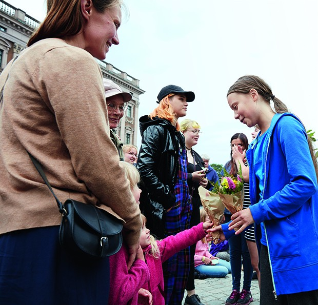 Cover feature of activist Greta Thurnberg protesting outside Swedish parliament, receiving flowers from children. (Foto: British GQ)