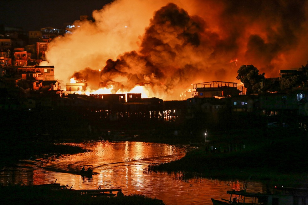O bairro de Educandos é visto envolvido pelas chamas durante um incêndio de grandes proporções em Manaus. — Foto: Michael Dantas/AFP