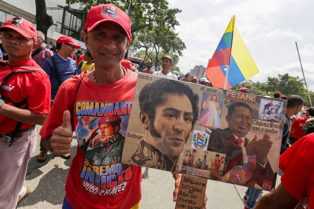 Manifestante pró-Maduro leva cartaz com imagens de Hugo Chavez e Simon Bolívar. — Foto: Cristian Hernandez / AFP