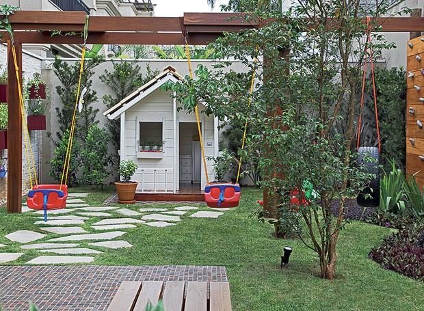 Um quintal pra filho nenhum botar defeito: ao fundo, a casinha de boneca tem telhas e piso de madeira de verdade. Do lado direito, ainda há uma parede de escalada (Foto: Evelyn Müller)