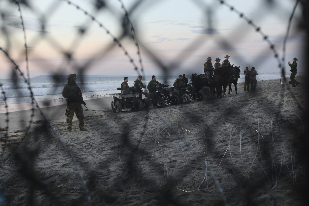 Agentes da polícia americana de fronteira são vistos de Tijuana, no México, através da cerca que divide os dois países — Foto: Rodrigo Abd/AP