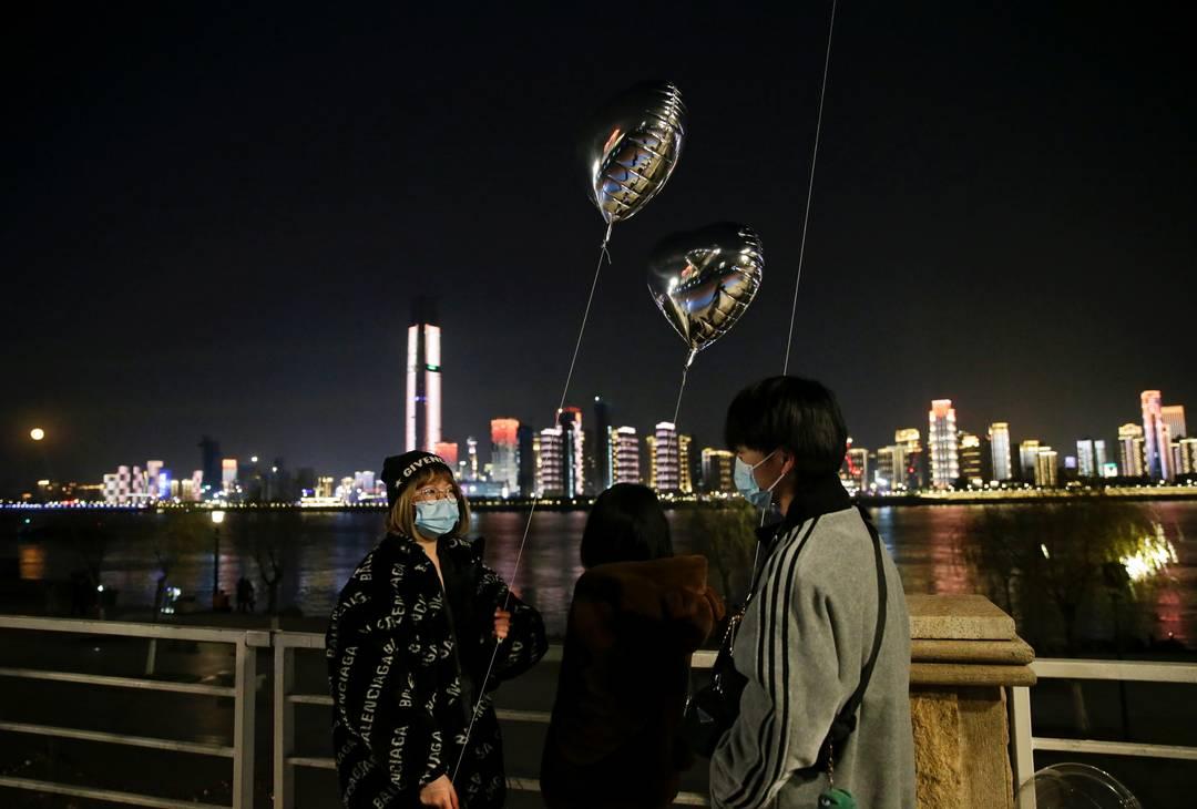 Em Wuhan, epicentro da pandemia de coronavírus, as pessoas usam máscara para esperar por 2021
