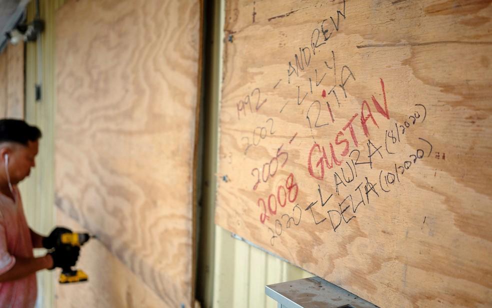 Bang Bui coloca tapumes de madeira em sua loja antes da chegada do furacão Delta, em Abbeville, Louisiana, na quinta-feira (8) — Foto: Reuters/Kathleen Flynn