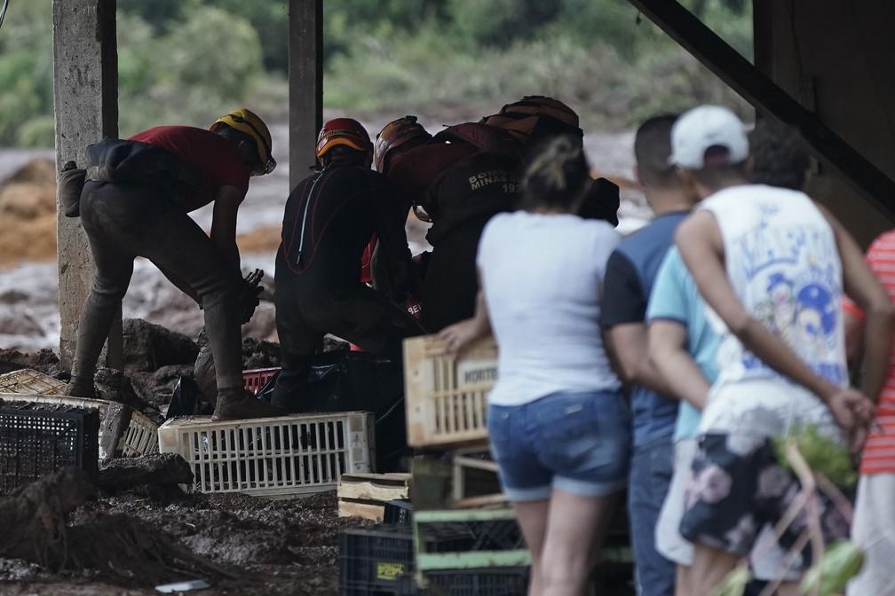 Bombeiros retiram um corpo da lama depois do rompimento da barragem da Vale em Brumadinho. — Foto: Leo Correa/AP