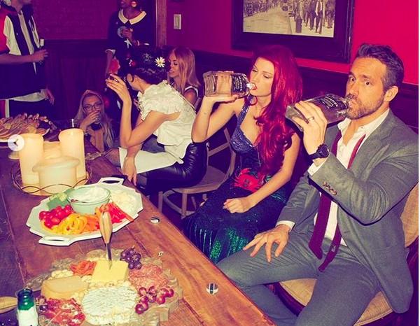 A cantora Taylor Swift vestida como a personagem Ariel do clássico A Pequena Sereia (2019), em sua festa de Ano Novo, e bebendo uíesque ao lado do ator Ryan Reynolds (Foto: Instagram)