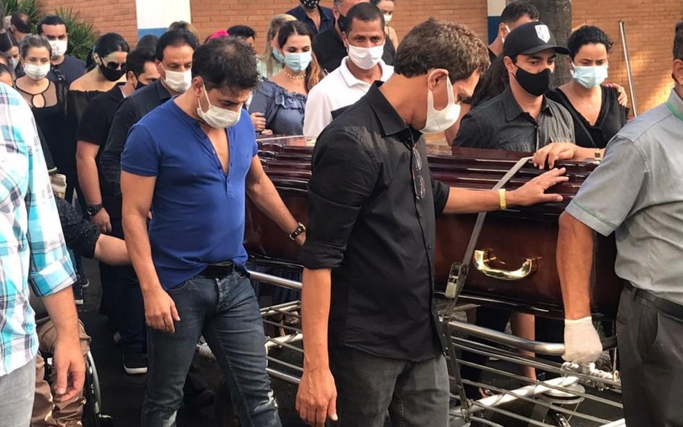 Zezé (de camisa azul marinho) ajuda a levar o corpo do pai durante o enterro — Foto: Vitor Santana/G1