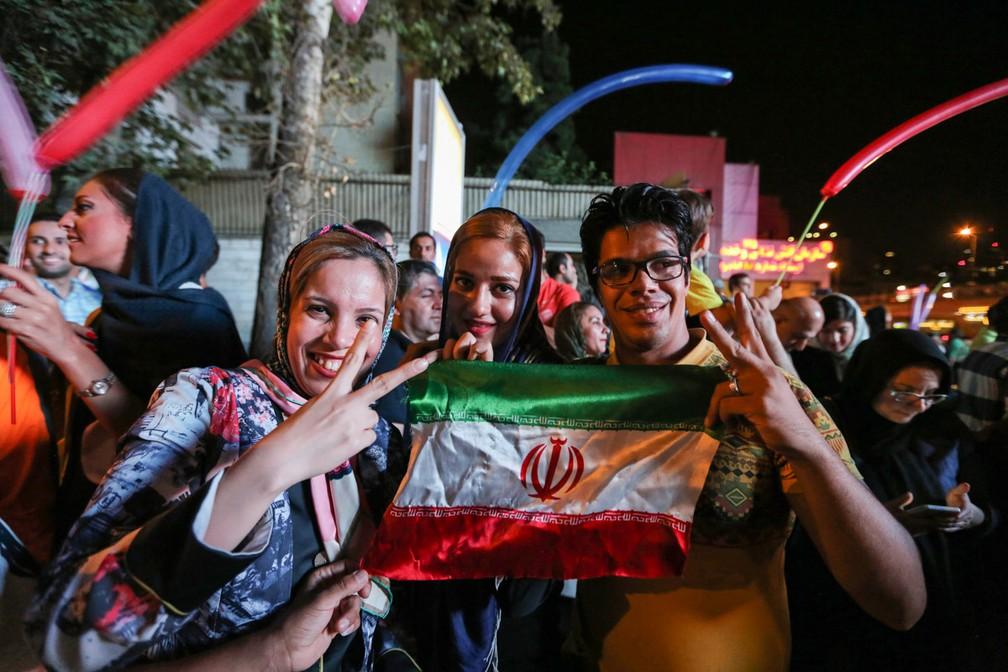 Iranianos seguram a bandeira de seu país e fazem o sinal da vitória ao comemorar o acordo sobre o programa nuclear em Teerã em 2015 (Foto: Atta Kenare/AFP)