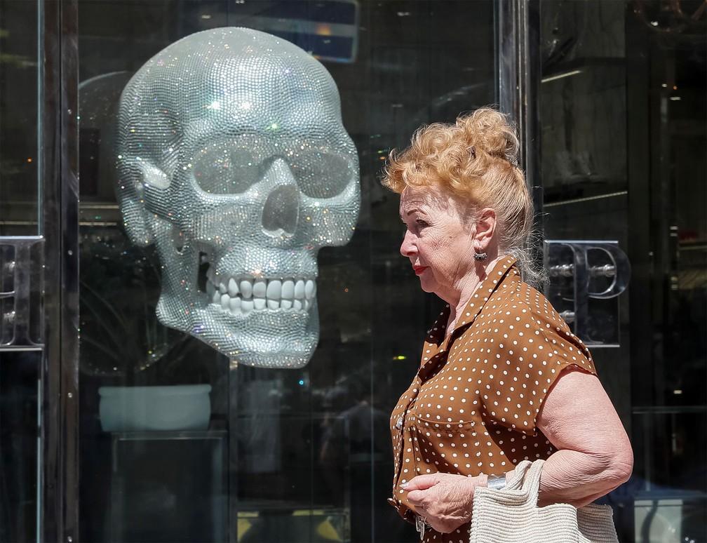 26 de junho - Mulher passa por escultura de um crânio gigante exibida em vitrine de Kiev, na Ucrânia — Foto: Gleb Garanich/Reuters