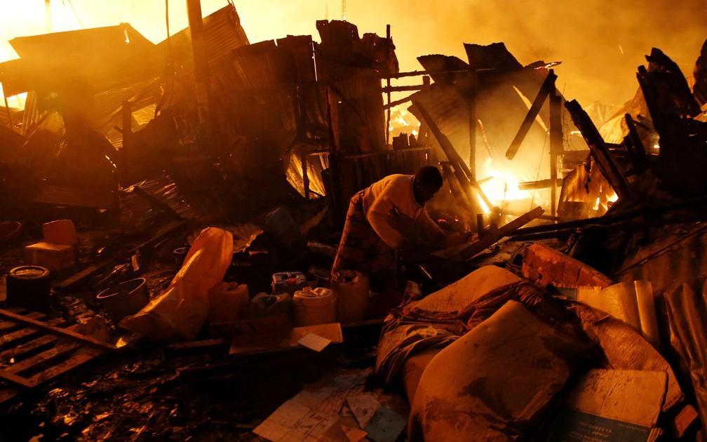 Moradora busca pertences nos destroços deixados por incêndio em favela de Nairobi, no Quênia, no domingo (28) (Foto: Thomas Mukoya/ Reuters)