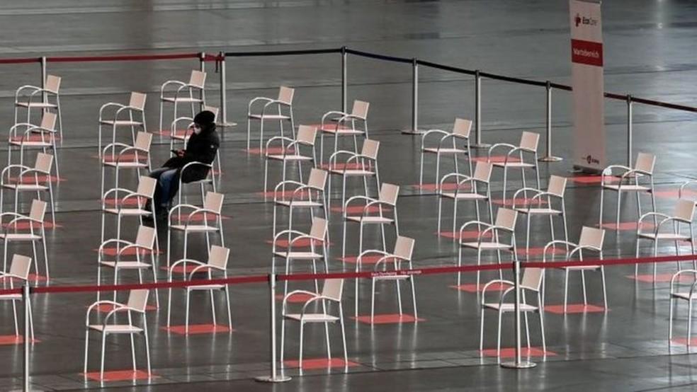 Um homem espera em um centro de vacinas na Alemanha, onde os cidadãos tem demonstrado alto grau de hesitação sobre se vacinar — Foto: Getty Images/BBC