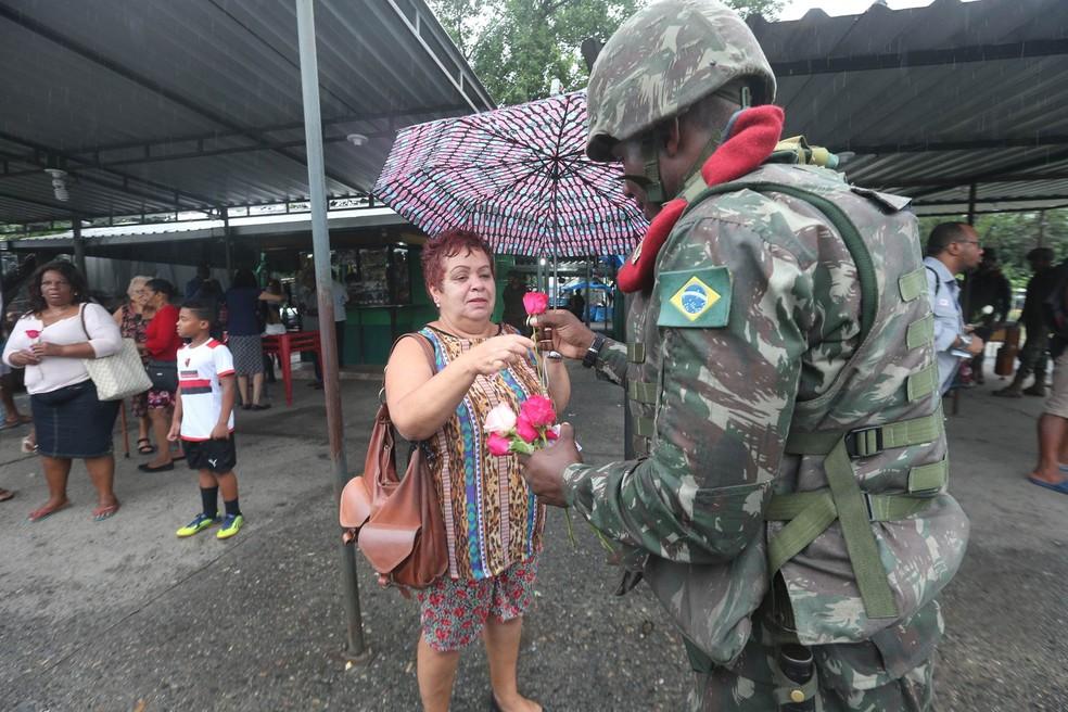 Militares do Exército entregam flores para mulheres para marcar o Dia Internacional da Mulher, na região da Vila Kennedy, na Zona Oeste do Rio de Janeiro (Foto: Wilton Junior/Estadão Conteúdo)