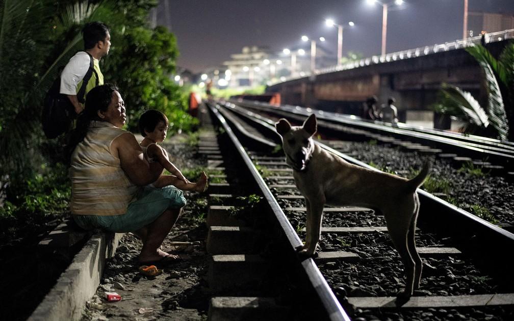 Foto de 19 de outubro mostra mãe com criança sentadas ao lado de linha de trem de Manila, aguardando para pegar um carrinho — Foto: Noel Celis/AFP