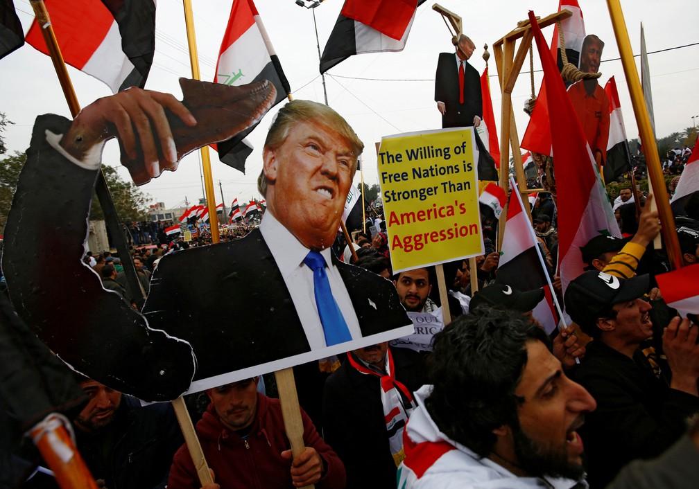 Apoiadores do clérigo xiita iraquiano Moqtada al-Sadr carregam cartaz com a foto do presidente dos Estados Unidos, Donald Trump, em um protesto em Bagdá, no Iraque, na sexta-feira (24)  — Foto: Alaa al-Marjani/ Reuters