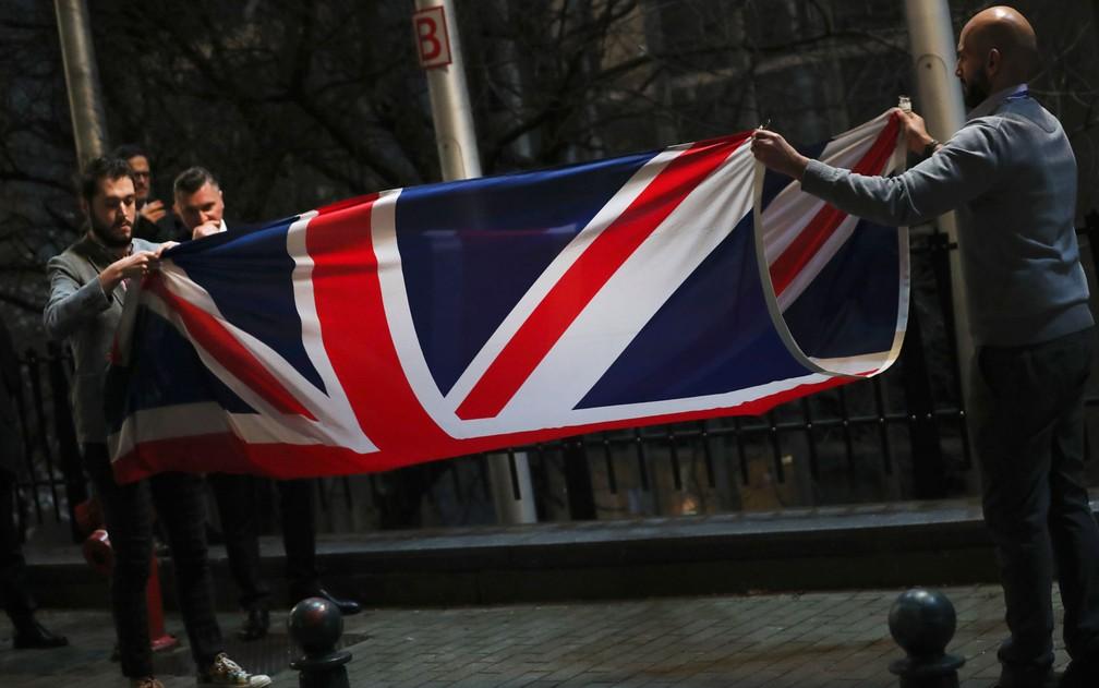 A bandeira do Reino Unido é dobrada e removida após ser baixada do lado de fora do Parlamento Europeu, em Bruxelas, na Bélgica, na noite do Brexit, em 31 de janeiro — Foto: AP Photo/Francisco Seco