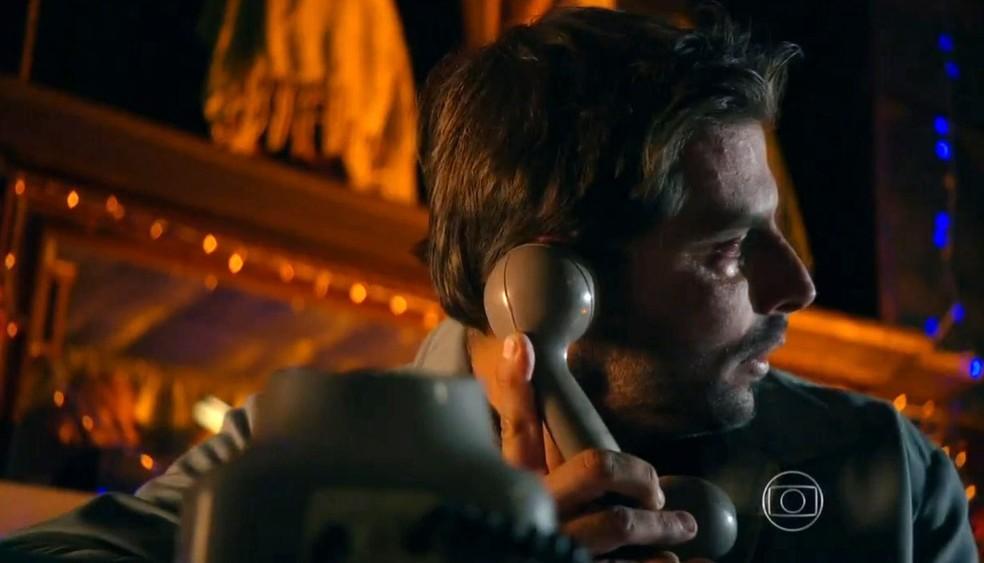 Cassiano (Henri Castelli) é obrigado a desligar o telefone na cara do pai por causa da chegada dos capangas de Dom Rafael (Cesar Troncoso), em 'Flor do Caribe' — Foto: Globo
