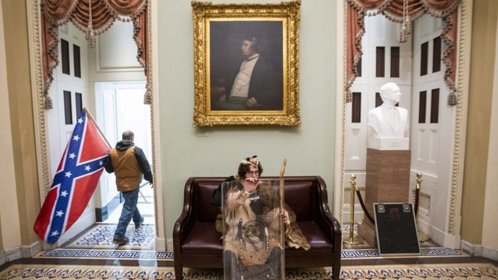 Homem com pele de urso, cajado e escudo policial descansa próximo a bandeira confederada e retrado de senador abolicionista em invasão ao congresso dos EUA — Foto: EPA/BBC