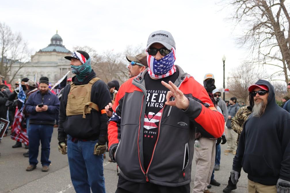 Homem identificado como integrante do grupo racista Proud Boys faz gesto associado à supremacia branca durante invasão ao Capitólio dos EUA, em 6 de janeiro — Foto: By Elvert Barnes from Silver Spring MD, USA - 24.ProudBoys.USSC.WDC.6January2021, CC BY-SA 2.0