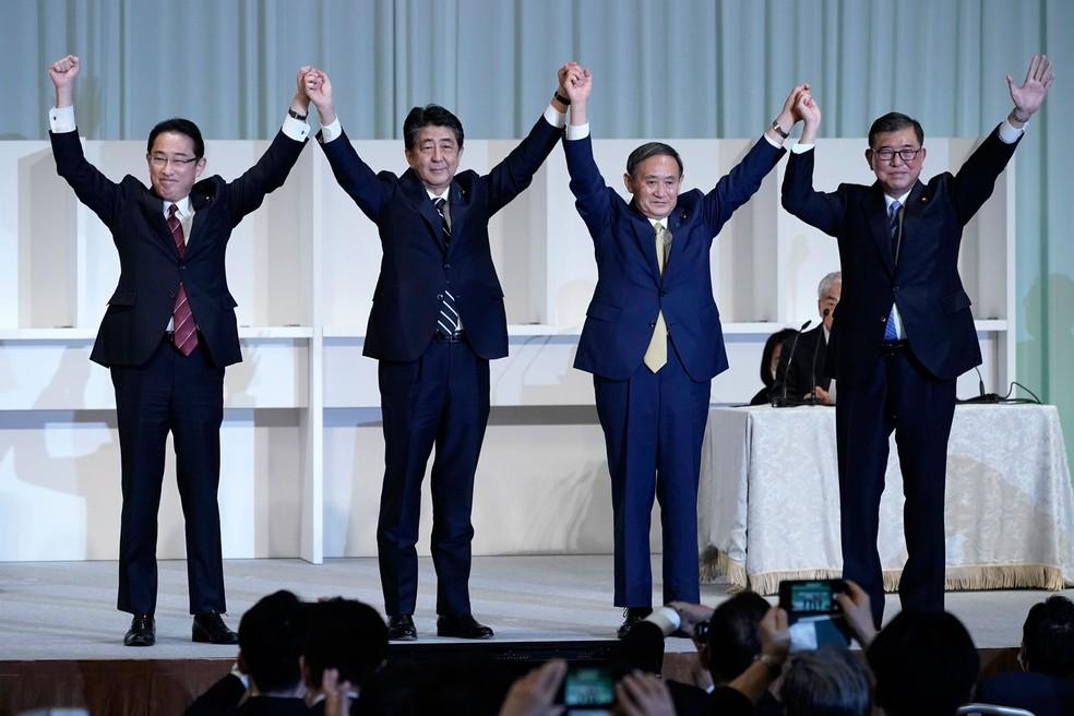 Ex-ministro das Relações Exteriores Fumio Kishida (à esquerda), o premiê do Japão, Shinzo Abe, Yoshihide Suga e o ex-ministro da Defesa Shigeru Ishiba comemoram a conclusão da eleição interna do Partido Liberal Democrático nesta segunda-feira (14) — Foto: Eugene Hoshiko/AP